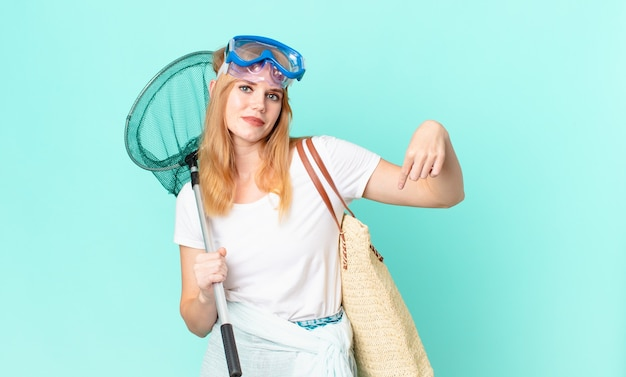 Bella donna dalla testa rossa con una rete da pesca e occhiali di protezione.