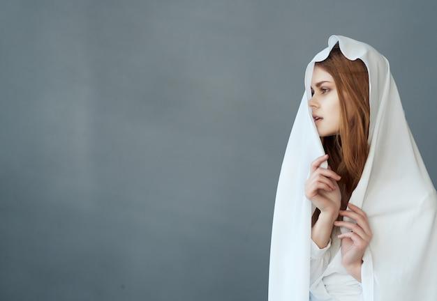 Una bella donna dai capelli rossi si copre la testa con un panno bianco
