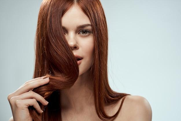 Donna graziosa della testarossa che tiene i suoi capelli