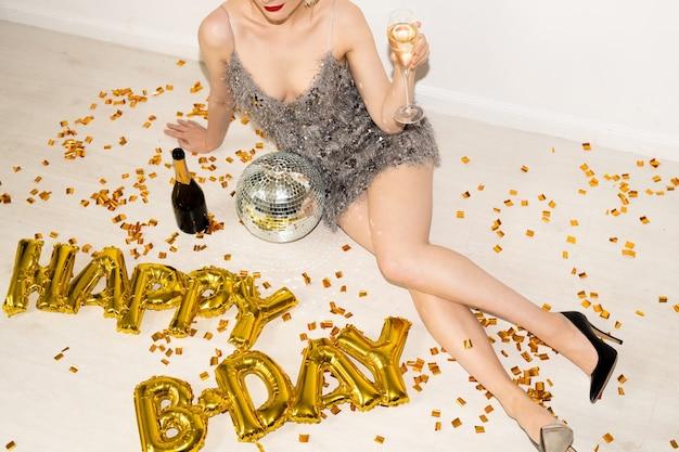 Ragazza abbastanza rilassata in abito glamour seduto sul pavimento tra coriandoli, discoball, bottiglia di champagne e palloncini a forma di lettera