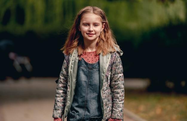 Ragazza graziosa della scuola nel ritratto del parco di autunno. bellissima allieva della scuola primaria all'aperto