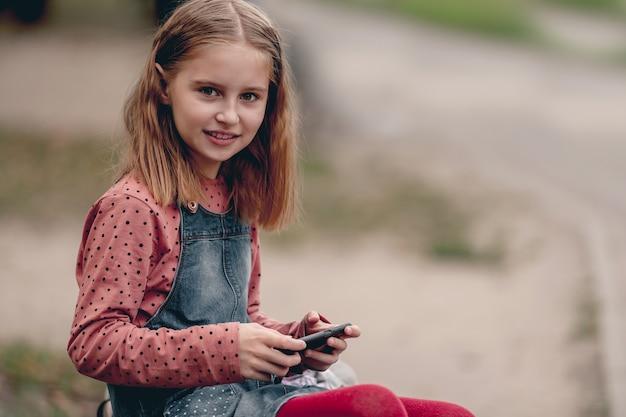 Ragazza graziosa della scuola che chiacchiera sullo smartphone all'aperto. una ragazzina carina comunica usando un moderno telefono cellulare nel parco autunnale