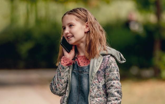 Ragazza graziosa della scuola che parla dallo smartphone all'aperto e che sorride. la ragazzina carina comunica usando il cellulare nel parco autunnale