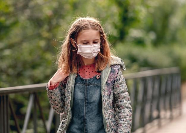 Bella ragazza della scuola che indossa la maschera facciale in piedi nel parco autunnale e che guarda l'obbiettivo. bella ragazzina dopo la scuola in tempo di pandemia di coronavirus covid