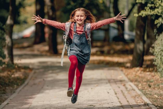 Ragazza graziosa della scuola con lo zaino che corre e ride. divertente allieva bambina felice dopo la lezione di educazione nel parco autunnale