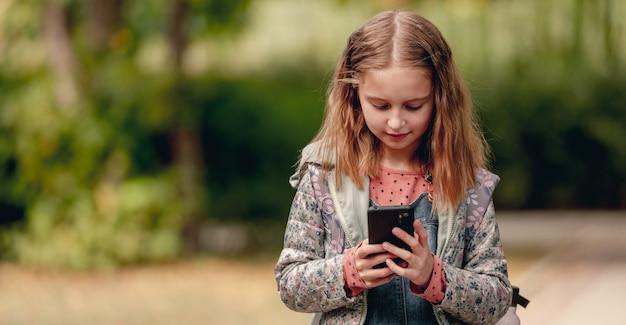 Ragazza graziosa della scuola con lo smartphone all'aperto. ragazza carina in piedi con il cellulare nel parco autunnale