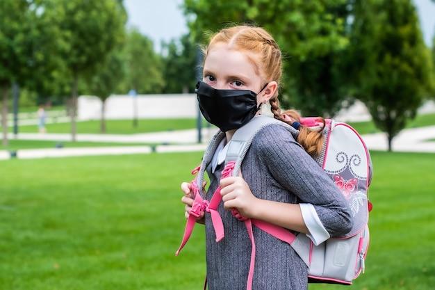 Una bella studentessa con i capelli rossi e una mascherina medica va a scuola. dietro le sue spalle c'è uno zainetto, sulla testa ci sono due trecce.