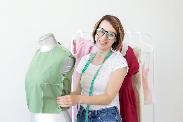 Una bella sarta con gli occhiali con un metro a nastro fa una camicetta verde con l'aiuto di un manichino da sarto e spille da balia. concetto di proprio laboratorio di cucito.