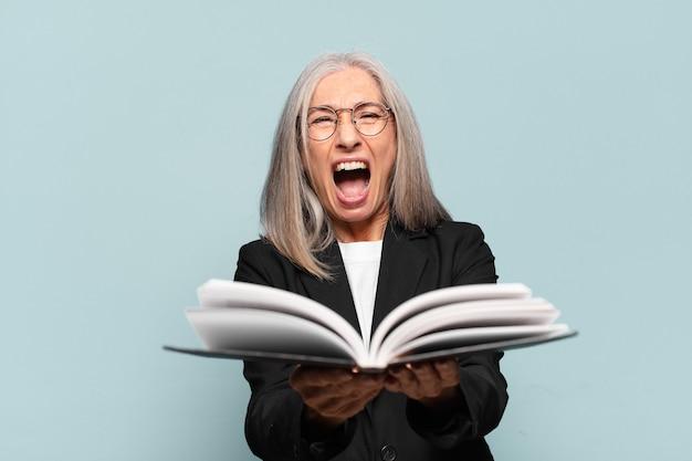 Donna di affari abbastanza maggiore con un libro