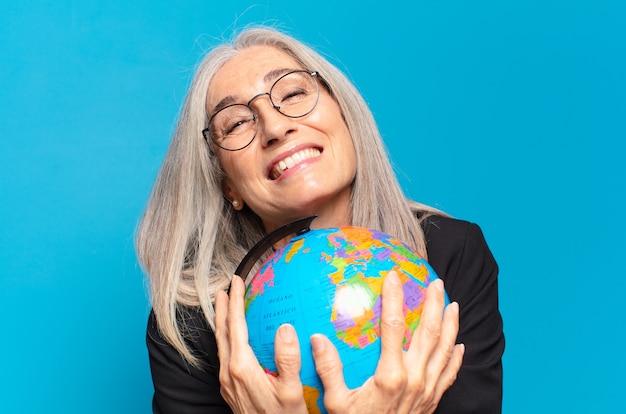 Donna abbastanza maggiore con un globo terrestre. concetto di mondo
