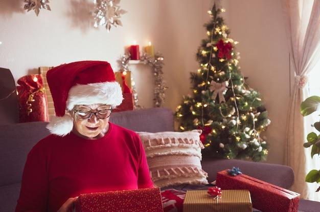 Una donna piuttosto anziana con un cappello da babbo natale apre il suo regalo di natale ed è stupita dalla sorpresa. albero di natale e regali per la famiglia che la circonda