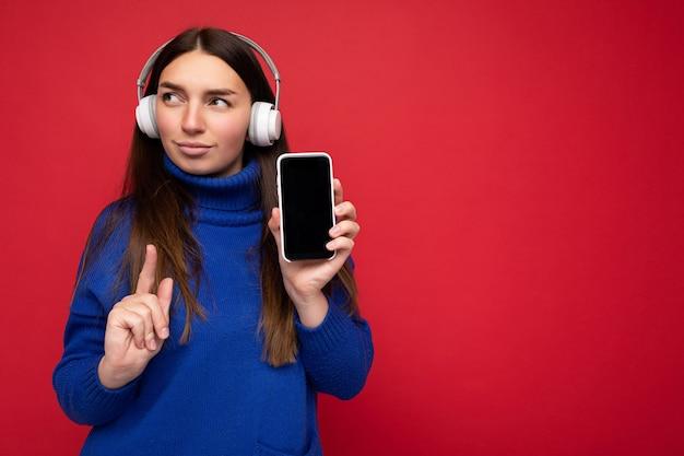 Giovane donna bruna concentrata abbastanza seria che indossa un maglione blu isolato su sfondo rosso