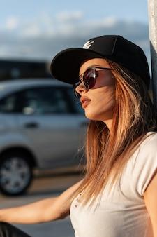 Ragazza americana abbastanza sexy in berretto nero alla moda in occhiali da sole vintage in abiti estivi che riposano sulla strada in una giornata di sole. ritratto bella ragazza sexy sul parcheggio all'aperto al tramonto.