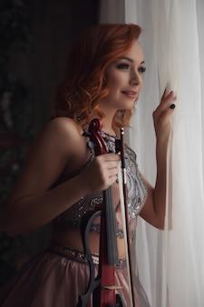 Giovane donna abbastanza snella con violino alla finestra