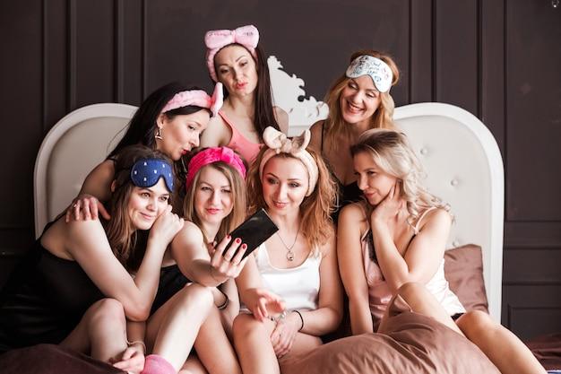 Belle, magre, affascinanti, eleganti, attraenti, allegre ragazze in pigiama che si godono la riunione al coperto che celebra la festa, l'evento, il compleanno che spara autoritratto sulla fotocamera frontale, utilizzando lo smartphone