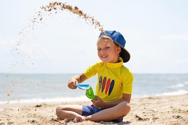 Ragazzo abbastanza sorridente che si siede sulla spiaggia e che gioca con il concetto di resto di sand.summer.