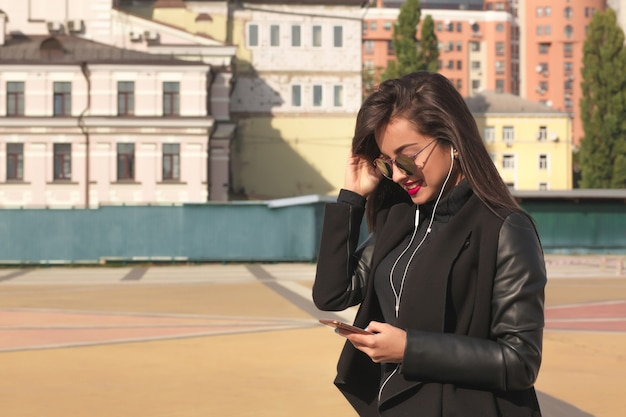 Donna castana abbastanza sorridente che guarda video sul telefono cellulare, in piedi sulla strada
