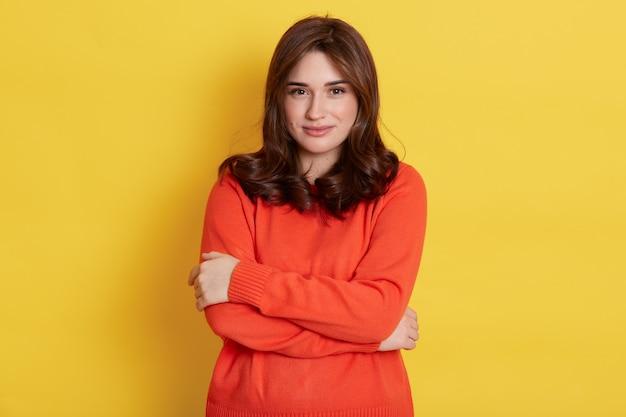 La donna europea abbastanza sorridente si abbraccia dolcemente, esprime amore per se stessa, si sente a suo agio, è di buon umore, isolata sul muro giallo