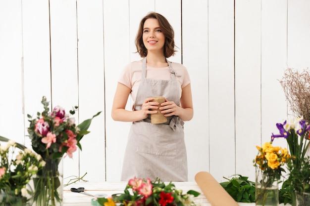 Donna fiorista abbastanza sorridente con fiori diversi