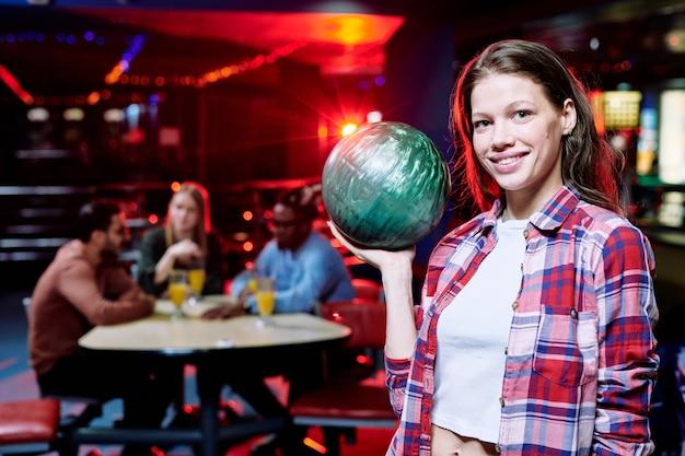 Bella ragazza sorridente in abbigliamento casual tenendo palla da bowling in piedi