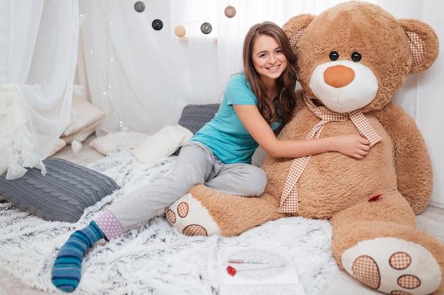 Ragazza abbastanza sorridente che si siede e che abbraccia il grande orso di peluche a casa
