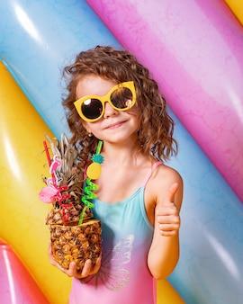 Bella ragazza sorridente che indossa costumi da bagno rosa e blu e sunglasse