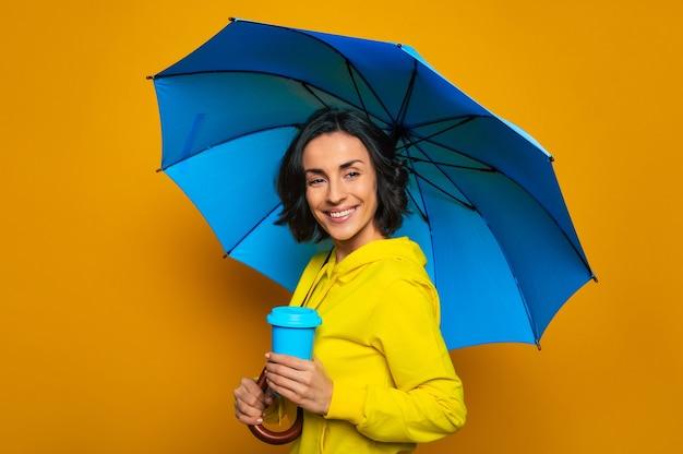 Bella ragazza sorridente in una giacca gialla sotto un ombrello, con una tazza termica blu nella mano sinistra, guardando dritto.