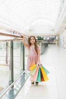 Bambina sorridente graziosa con i sacchetti della spesa che posano nel negozio. incantevoli momenti dolci della piccola principessa, un bambino piuttosto amichevole che si diverte alla macchina fotografica