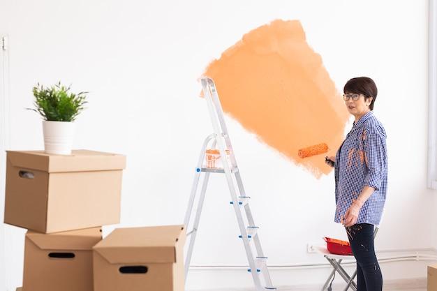 Donna di mezza età abbastanza sorridente pittura parete interna della casa con rullo di vernice.