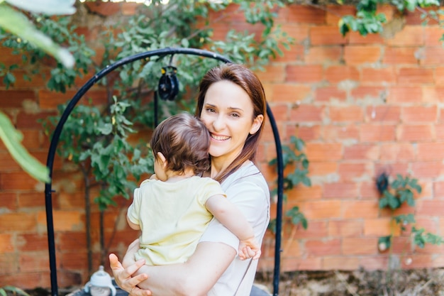 Madre millenaria abbastanza sorridente che tiene in braccio il suo bambino di un anno