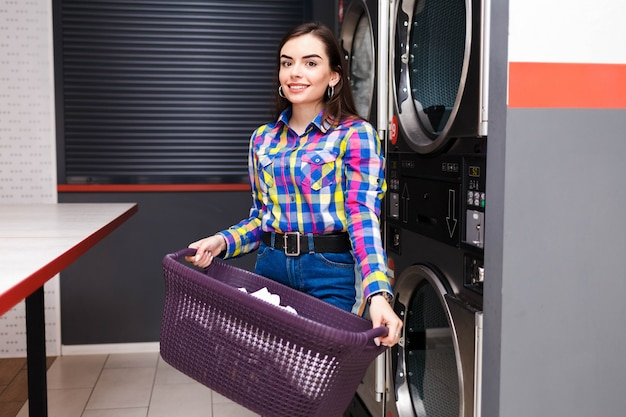 La donna sorridente graziosa alla lavanderia automatica tiene un cestino dei vestiti.
