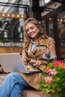 Donna abbastanza sorridente in trench che lavora con gioia al computer portatile mentre si tiene la carta di credito in mano all'aperto presso la terrazza del caffè