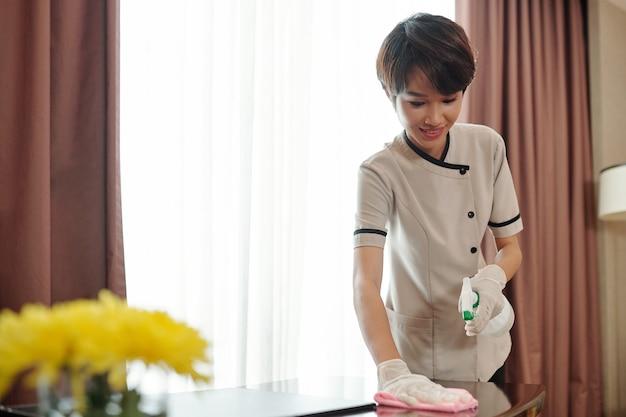 Giovane cameriera asiatica abbastanza sorridente con guanti di lattice che pulisce mobili con liquido disinfettante