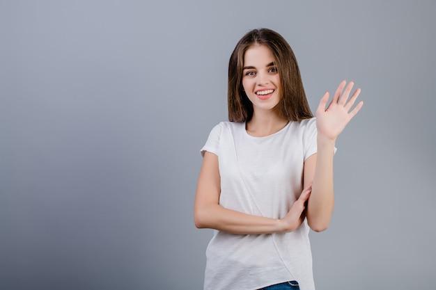 Mano d'ondeggiamento abbastanza sorridente della giovane donna isolata sopra la parete grigia