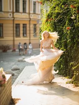 Giovane donna abbastanza sorridente con capelli biondi lunghi in vestito leggero volante elegante che corre lungo la strada