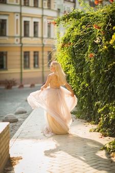 Giovane donna abbastanza sorridente con lunghi capelli biondi in elegante abito leggero volante che corre lungo la strada