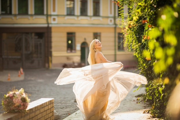 Giovane donna abbastanza sorridente con lunghi capelli biondi in un elegante vestito leggero volante che corre lungo la strada