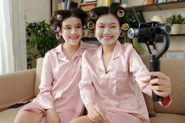 Giovani donne abbastanza sorridenti in pigiama che si fanno selfie con bigodini e maschera di argilla disintossicante addosso