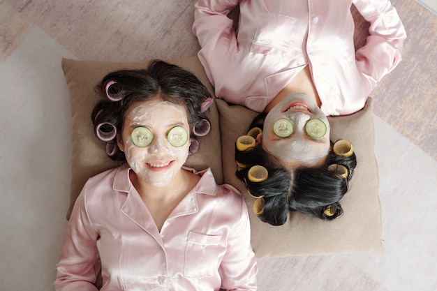 Giovani donne abbastanza sorridenti con maschera di argilla e fette di cetriolo che si rilassano sui cuscini vista dall'alto
