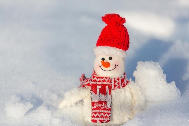 Pupazzo di neve grazioso su priorità bassa nevosa della data