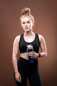 Bella sportiva con capelli ricci biondi che tiene la bottiglia di plastica con la bevanda blu pur avendo una pausa tra gli allenamenti in isolamento