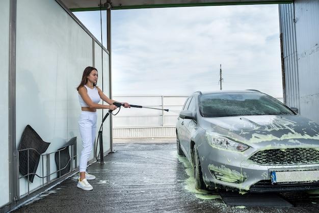 Donna abbastanza sportiva che pulisce con schiuma la sua ruota con pistola ad alta pressione. stile di vita