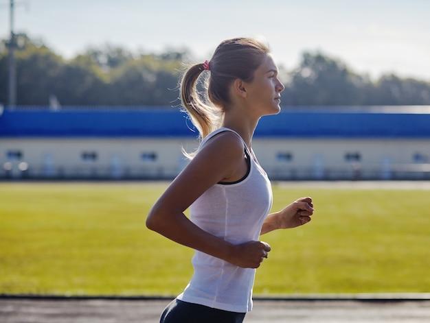 Donna abbastanza sportiva che pareggia al parco nella luce dell'alba