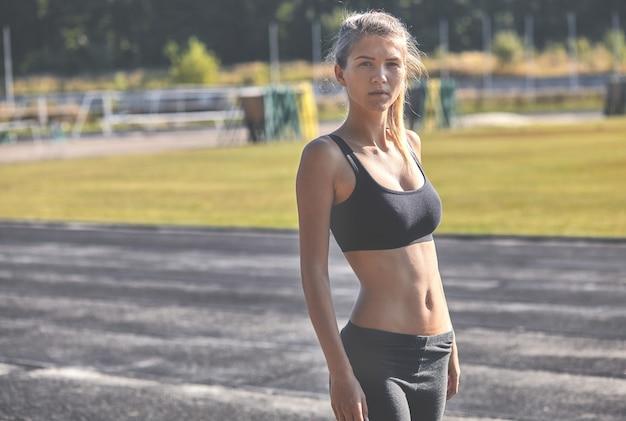 Una donna abbastanza sportiva in piedi nel parco nella luce dell'alba