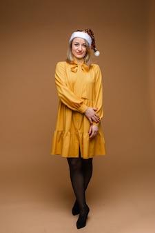Donna abbastanza srylish in cappello di natale andres vestito giallo, immagine isolata sulla parete gialla