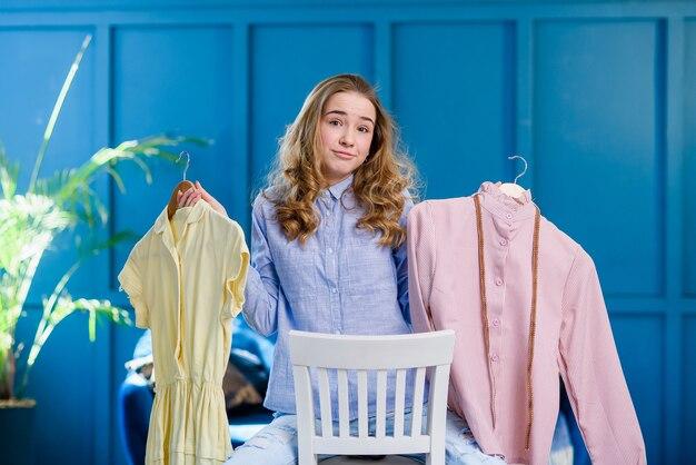 Ragazza studentessa carina sentirsi incerta sulla scelta del miglior vestito per il ballo di fine anno. la giovane donna decide tra due abiti sui ganci nelle sue mani.