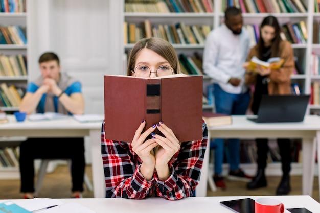 Ragazza graziosa dello studente che nasconde il suo fronte sopra il libro aperto sullo spazio moderno della biblioteca dell'istituto universitario e sugli amici multietnici che studiano insieme