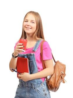 Studente grazioso con una tazza di caffè e quaderni su bianco