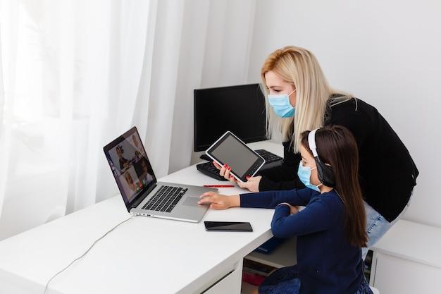 Studentessa abbastanza elegante che studia i compiti di matematica durante la sua lezione online a casa, distanza sociale durante la quarantena, autoisolamento, concetto di educazione online, scolaro a casa