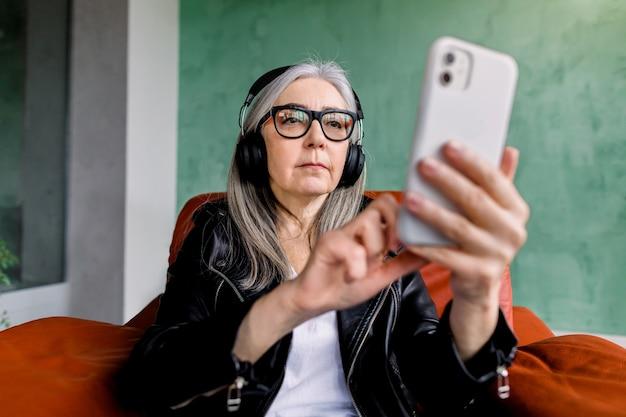 Signora senior abbastanza alla moda in occhiali con capelli grigi dritti che si siede nella sedia rossa e ascolta bella musica in cuffia dalla sua playlist smartphone